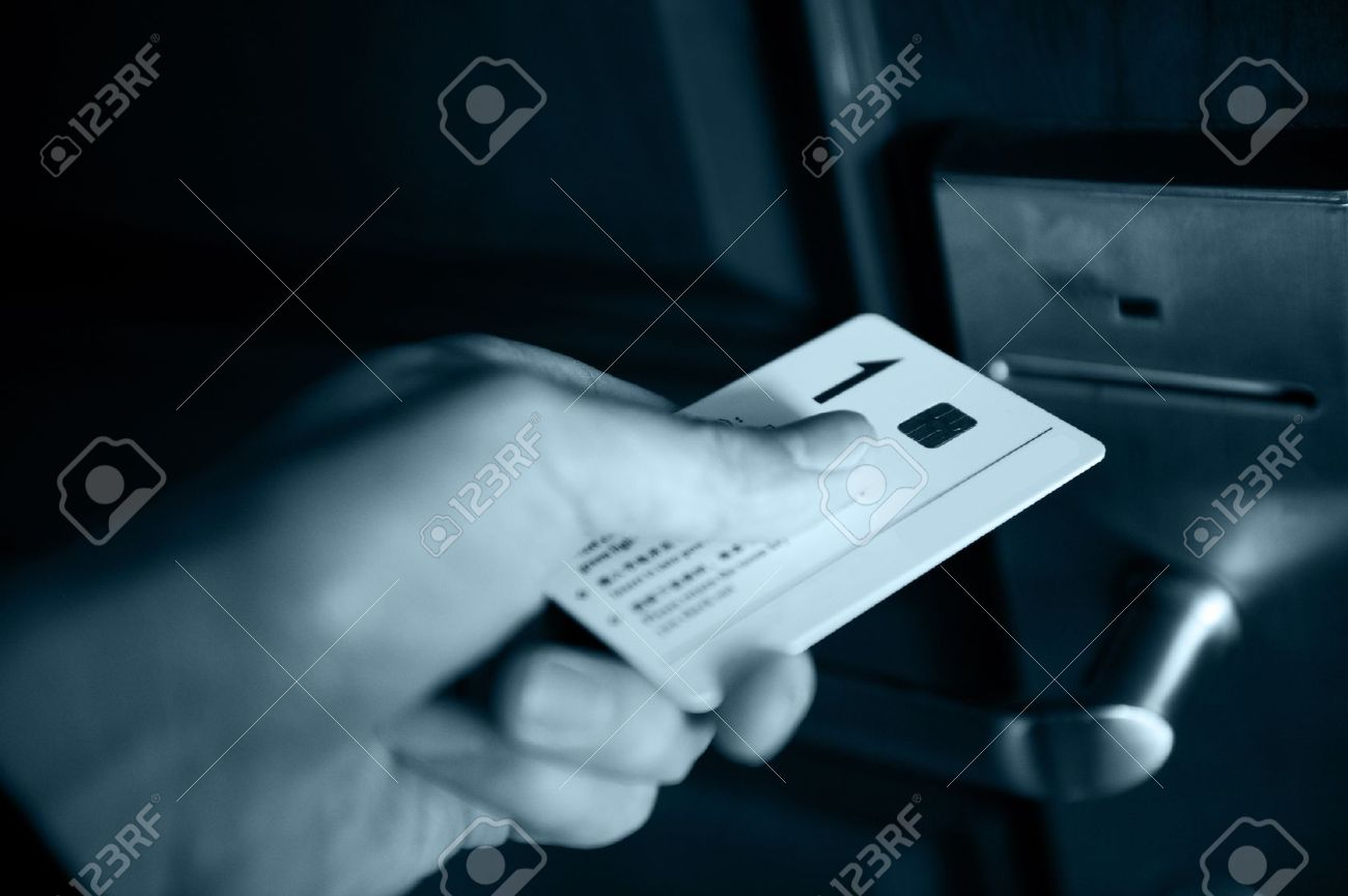 13955075-A-hand-inserting-keycard-in-the-electronic-lock-blue-tone--Stock-Photo