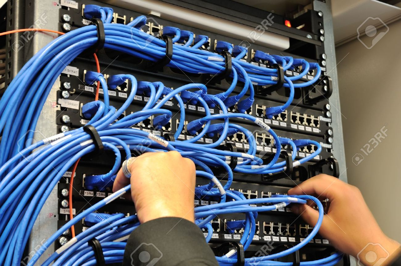 14054783-Man-connecting-network-cables-to-switches-Stock-Photo-network-cable-data