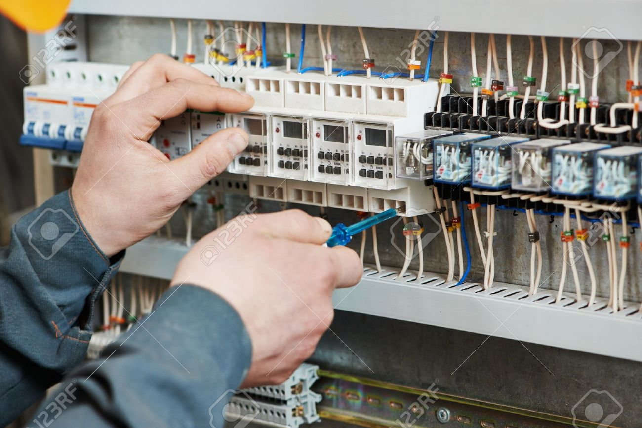 26774089-Hands-of-electrician-with-screwdriver-tighten-up-switching-electric-actuator-equipment-in-fuse-box-Stock-Photo