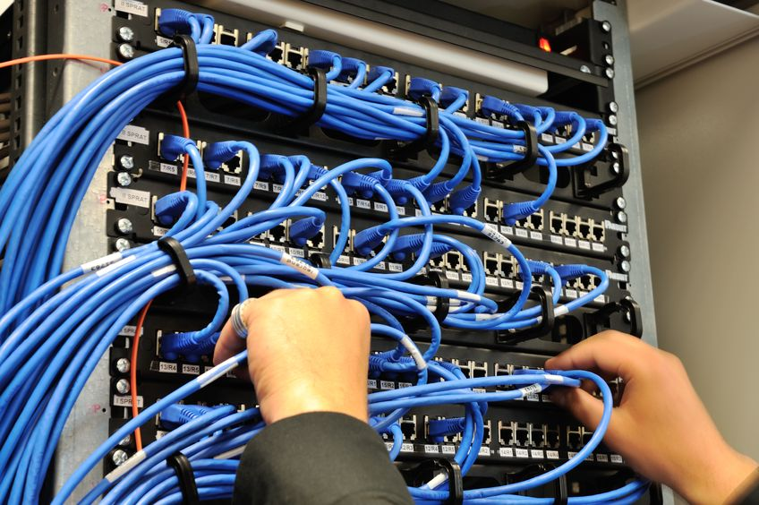 14054783 - man connecting network cables to switches