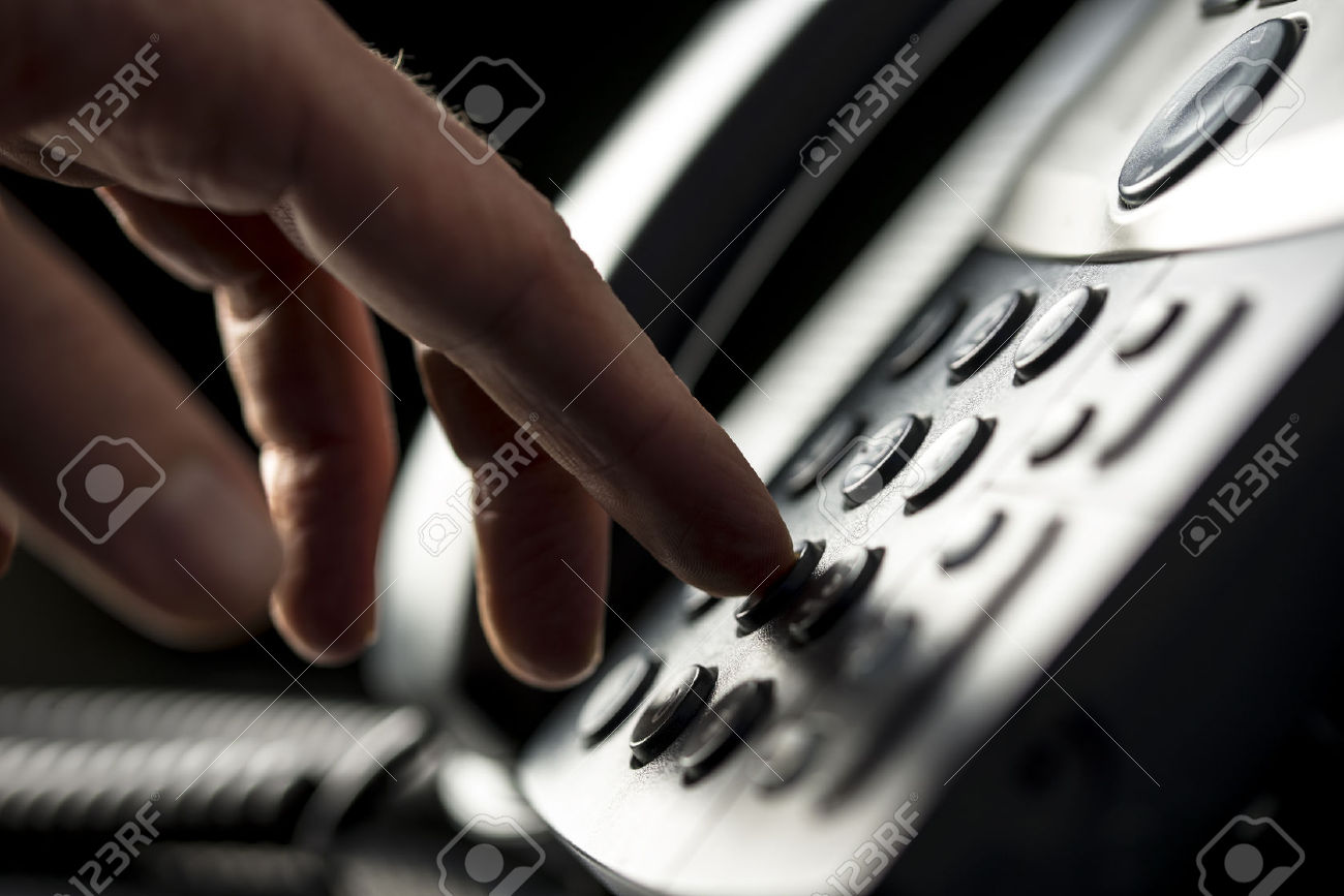 25651252-Closeup-view-of-the-hand-of-a-man-making-a-telephone-call-on-a-desktop-instrument-pressing-the-numbe-Stock-Photo