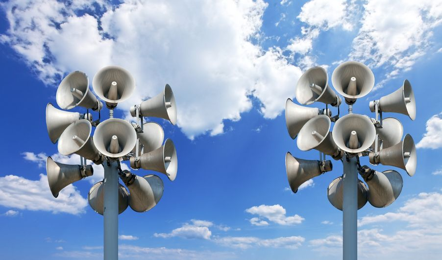 9526086 - many loudspeakers against blue, cloudy sky